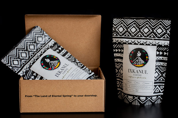 Ixkanul Coffee's monthly subscription box consisting of two bags of coffee with a design of mayan patterns