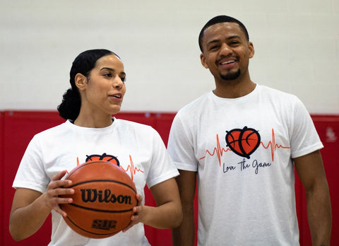 Male and Female basketball player holding basketball while laughing