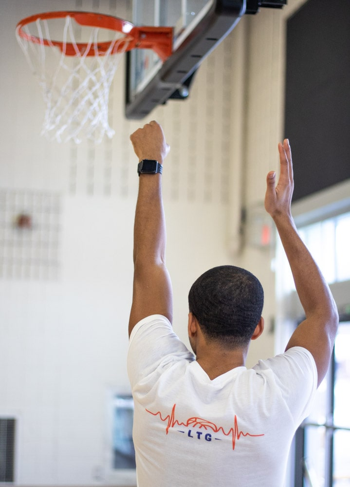 male basketball player holds follow through after shot. wearing white love and basketball basketball shirt