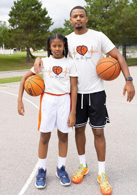 male hooper stands with female hooper holding basketballs while wearing white love and basketball collection shirts