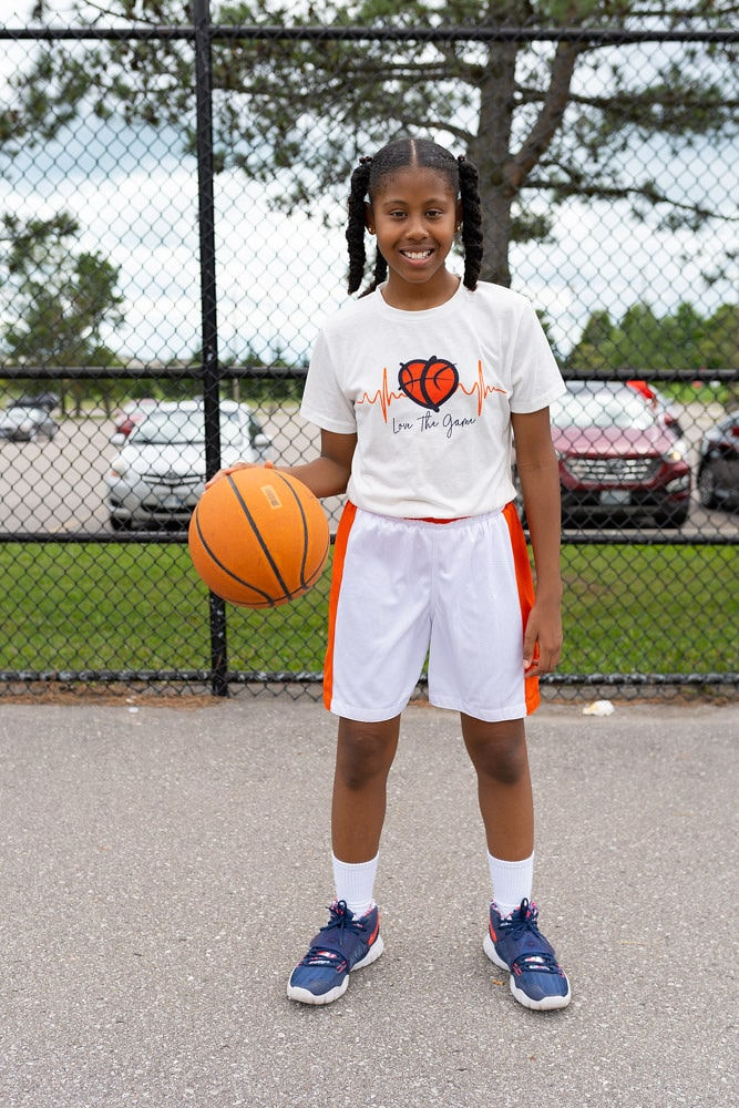 female basketball player dribbling basketball. while wearing white love and basketball collection shirts