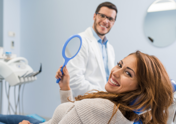Women smiling in a dentist chair holding a mirror