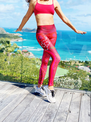 Billows of red clouds set amidst pink snakeskin, dusted with snakes and red butterflies on these compression leggings
