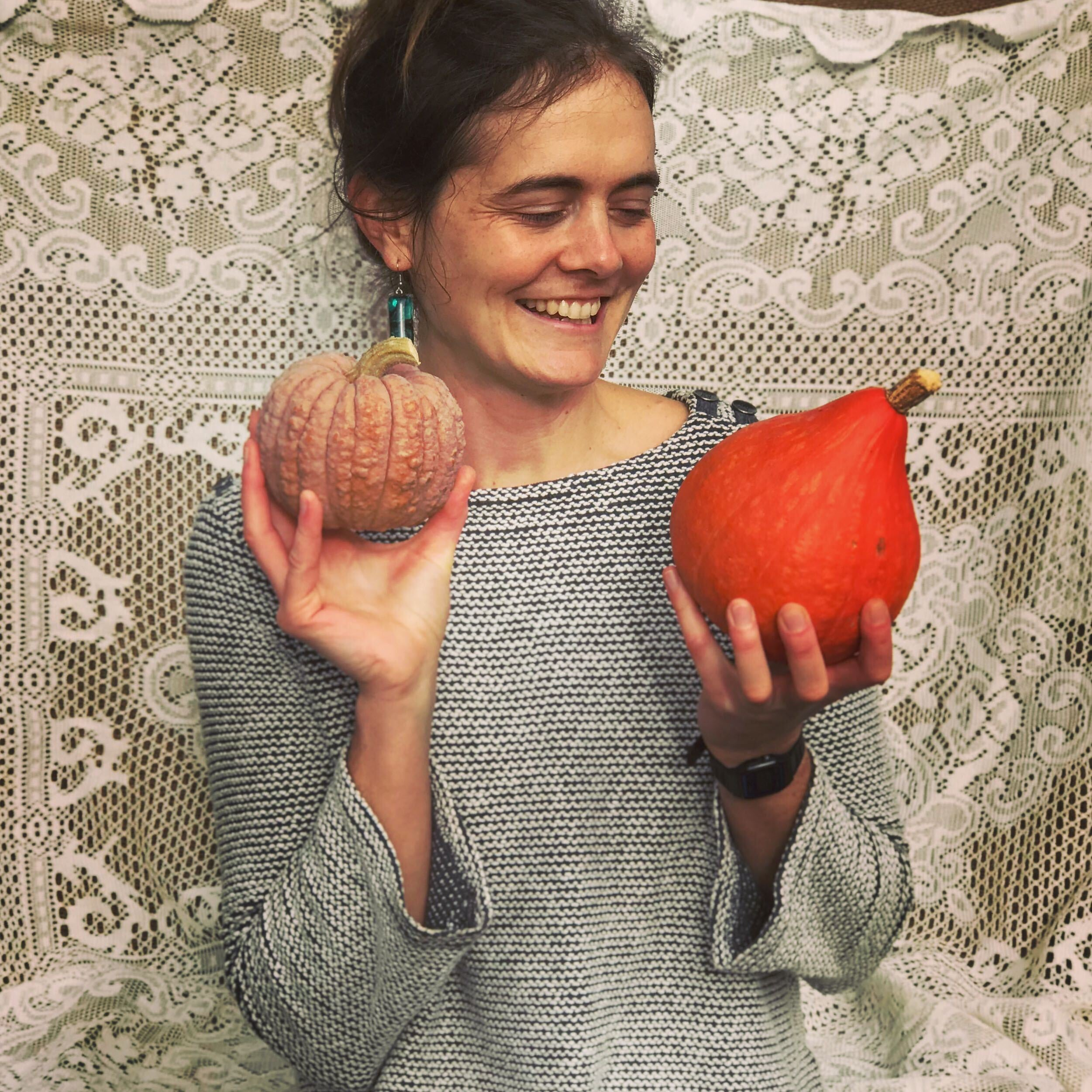 Michaela Hammer smiling and inspecting winter squash