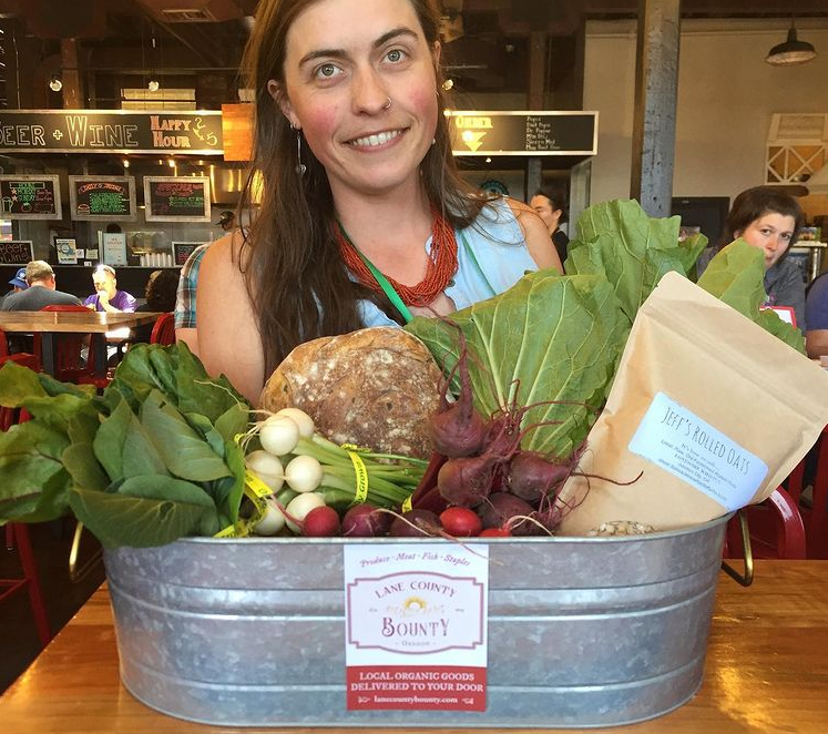 Shelley Bowerman smiles in front of a tub of artfully arranged vegetables with Lane County Bounty flyer