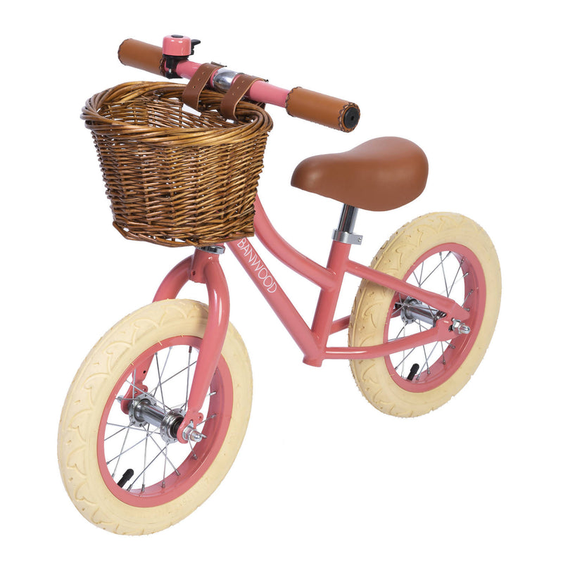 Banwood bike in Coral with brown wicker basket and white wheels