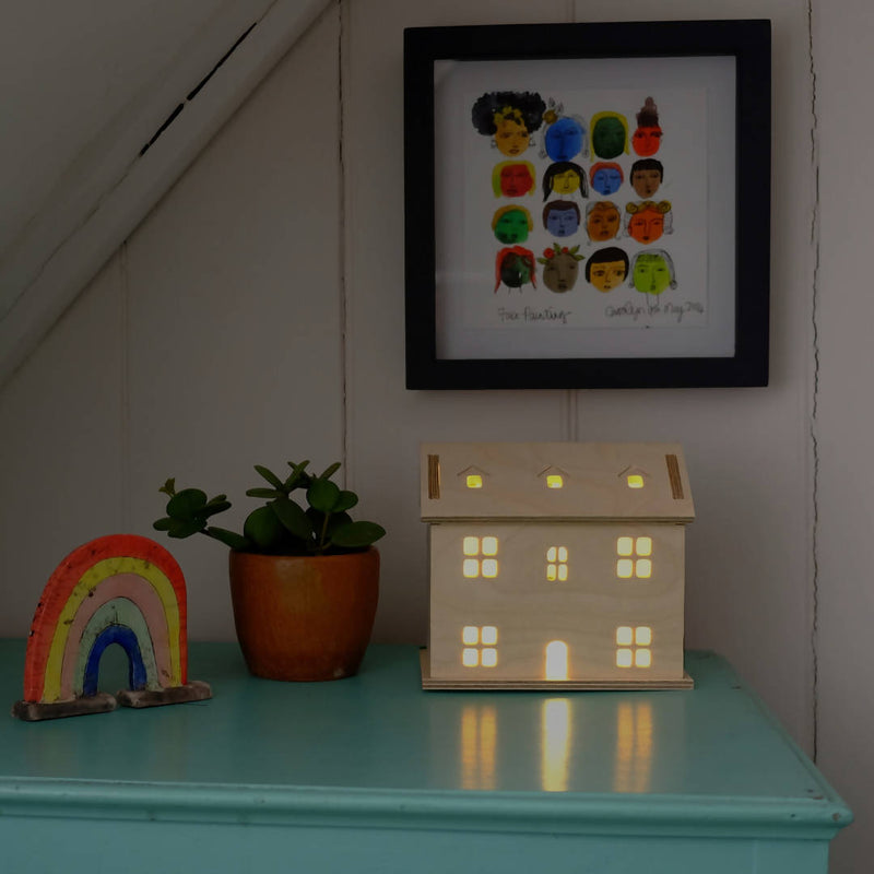 Welsh Cottage Light on shelf with rainbow and plant