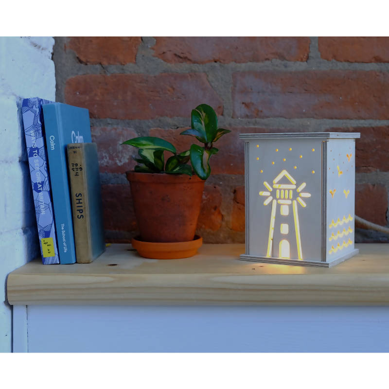 Lighthouse light on shelf with books and plant