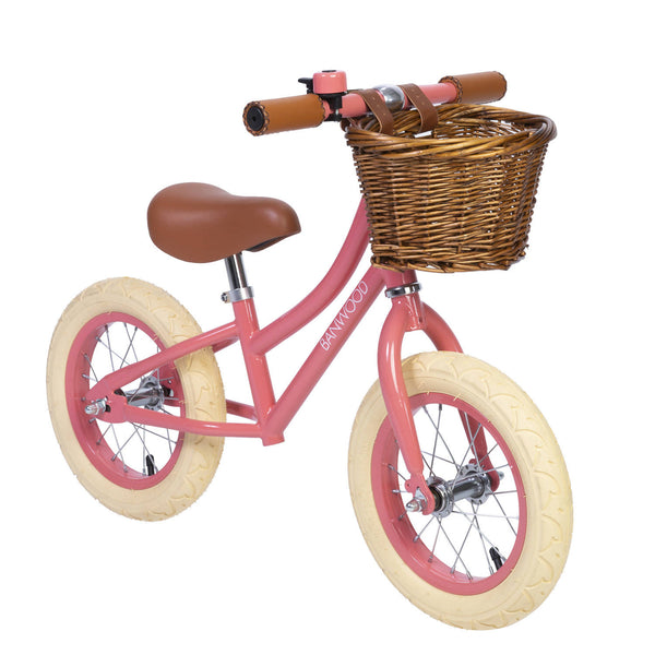 Coral Banwood bike with brown wicker basket and white wheels