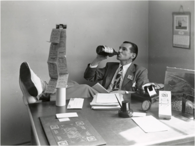 man drinking at desk