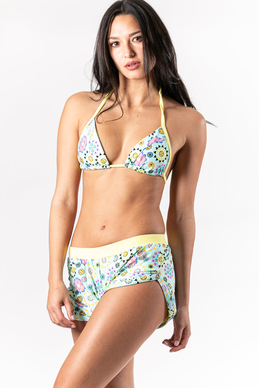 Two pieces sporty bikini with shorts pants in floral print and yellow tones. Sustainable Swimwear made from recycled plastics and bottles by BRISSUS