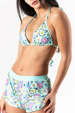 Two pieces sporty bikini with shorts pants in floral print and turquoise tones. Sustainable Swimwear made from recycled plastics and bottles by BRISSUS