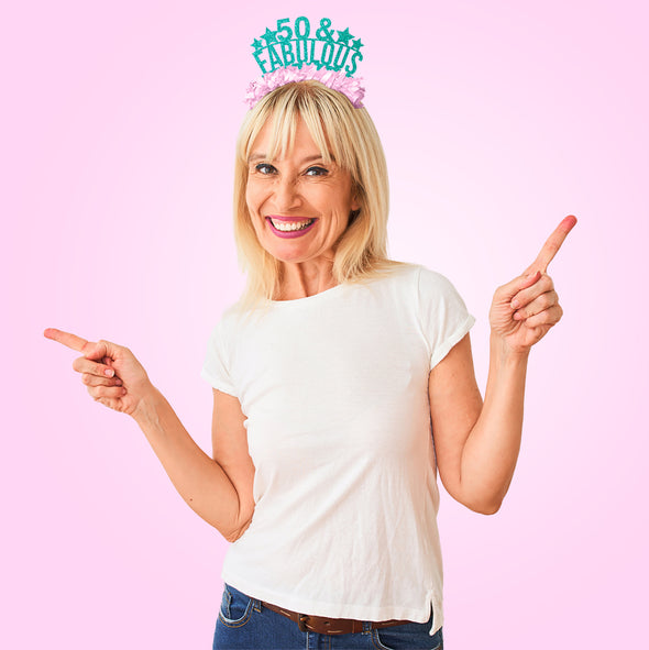 "Woman wearing teal and light pink fringe party crown saying ""50 & Fabulous"""