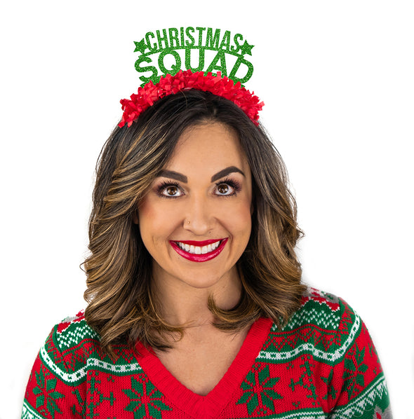 Girl dressed in Christmas sweater wearing a Green glitter party crown with red fringe saying Christmas Squad