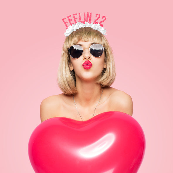 "Sassy woman with heart shaped balloon wearing hot pink and white fringe party crown saying ""Feelin 22"""