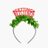 "Red glitter party crown with green fringe saying ""Getting Blitzened"" and has two small stars"