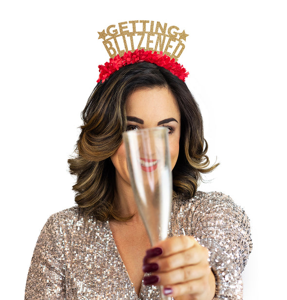"Girl wearing gold dress and holding a champagne glass wearing a  gold glitter and red fringe party crown that says ""Getting Blitzened"""