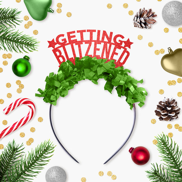 "Red glitter party crown with green fringe saying ""Getting Blitzened"" and has two small stars surrounded by Holiday decor"