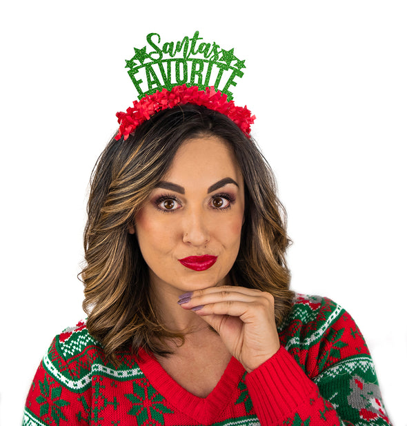 "Girl wearing Christmas sweater and Green glitter and red fringe party crown that says ""Santa's Favorite"" ""Santa's"" is in cursive"