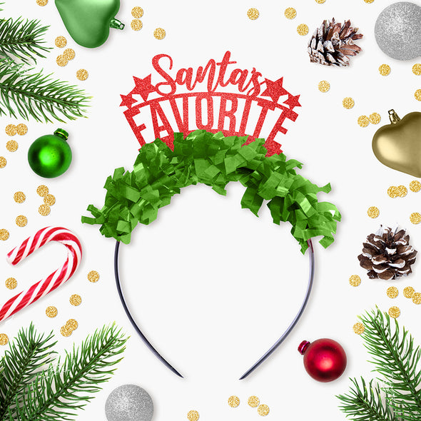 "Red glitter and green fringe party crown that says ""Santa's Favorite"" ""Santa's"" is in cursive surrounded by Christmas Decor"