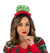 "Girl wearing Christmas sweater Green glitter  holiday party crown with red fringe saying ""Son of A Nutcracker"" and has two small stars"