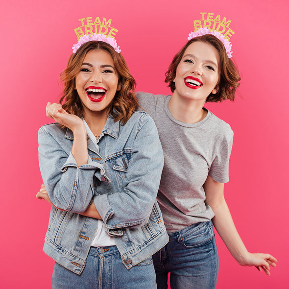 "Two best friends wearing matching gold glitter and pink fringe party crown that say ""Team Bride"". Image"