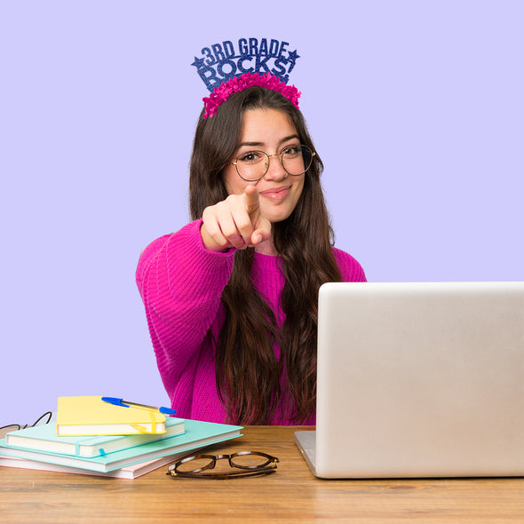"Teacher on laptop wearing blue glitter and hot pink party crown that says ""3rd Grade Rocks!"" Image"