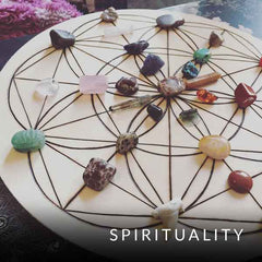 Blog category image of wooden flower of life grid with crystals placed on top