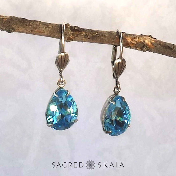 Vintage-style Aphrodite Crystal Teardrop Earrings with oxidized silver settings, lever back ear wires and pear-shaped aquamarine Swarovski crystals, shown hanging on a branch