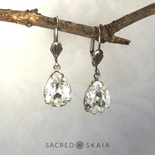 Aphrodite Crystal Teardrop Earrings with oxidized silver settings, lever back ear wires and pear-shaped clear Swarovski crystals, shown hanging on a branch as an alternate color choice