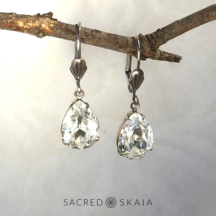 Vintage-style Aphrodite Crystal Teardrop Earrings with oxidized silver settings, lever back ear wires and pear-shaped clear Swarovski crystals, shown hanging on a branch