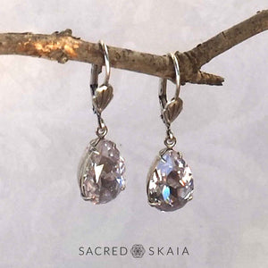 Vintage-style Aphrodite Crystal Teardrop Earrings with oxidized silver settings, lever back ear wires and pear-shaped smoky mauve (pale lavender gray) Swarovski crystals, shown hanging on a branch