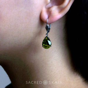 Aphrodite Crystal Teardrop Earrings with oxidized silver settings, lever back ear wires and pear-shaped olivine (dark olive green) Swarovski crystals, shown on a model with pierced ears