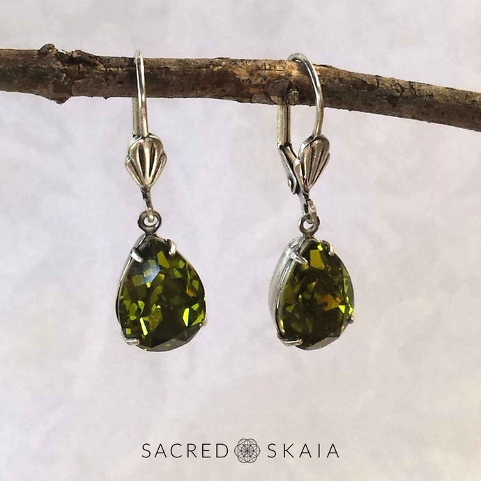 Vintage-style Aphrodite Crystal Teardrop Earrings with oxidized silver settings, lever back ear wires and pear-shaped olivine (dark olive green) Swarovski crystals, shown hanging on a branch