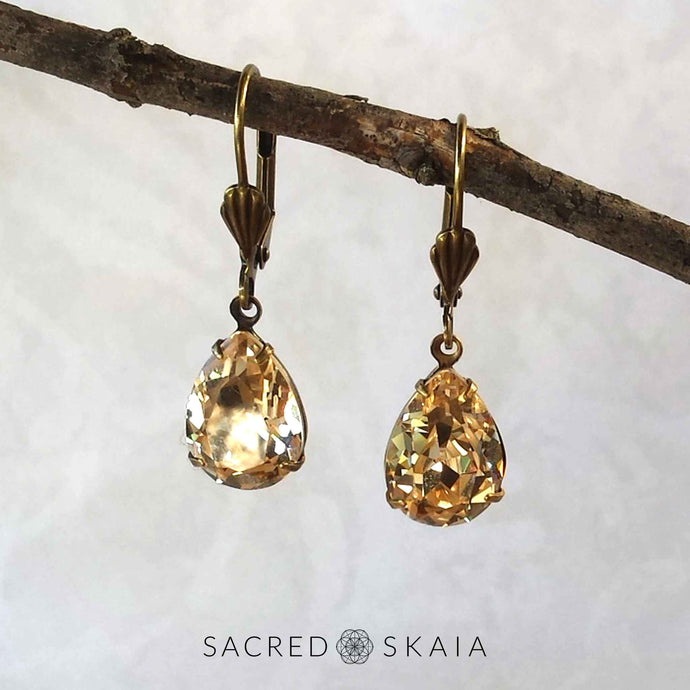 Vintage-style Aphrodite Crystal Teardrop Earrings with oxidized brass settings, lever back ear wires and pear-shaped light silk (pale gold) Swarovski crystals, shown hanging on a branch