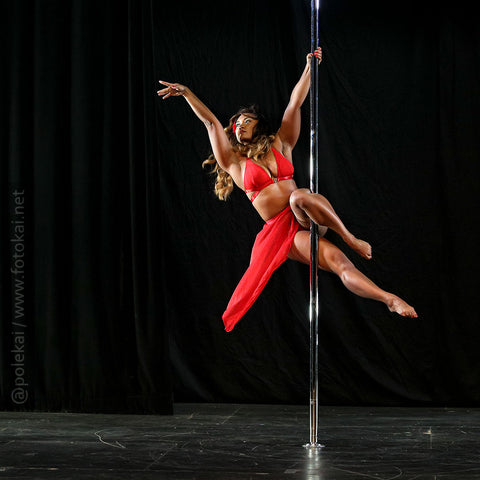 woman pole dancing in a red outfit