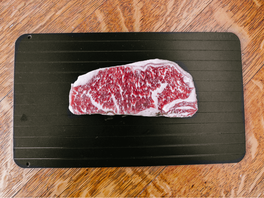 Wagyu New York Strip steak from W. Black Wagyu Farms via Crowd Cow frozen solid defrosting on a Family Size ThawTable the best way to defrost steak