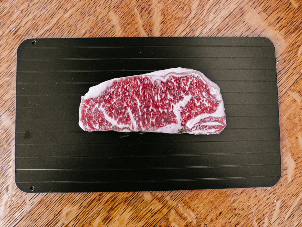 ThawTable - Defrosting Food Reimagined - What's the Best Way to Thaw Wagyu New York Strip Steaks? 12oz Wagyu NY Strip steak from W.Black Wagyu Farm via Crowd Cow sustainable meat delivery box frozen before dinner