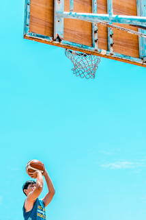 Young man perfecting his jumper at outside basketball court.