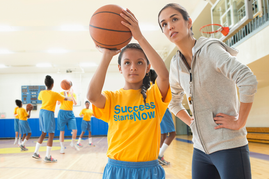 Young basketball player getting instruction on her shot from her coach.
