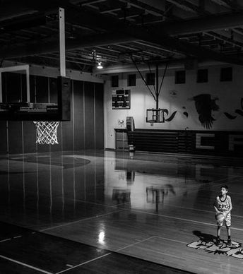 Young boy working on his free throw, perfecting his shot.