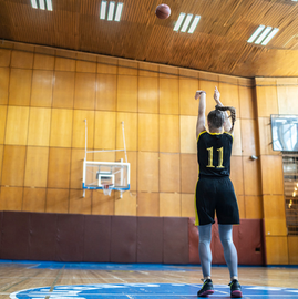 Lefty female shooting basketball from deep with good form.
