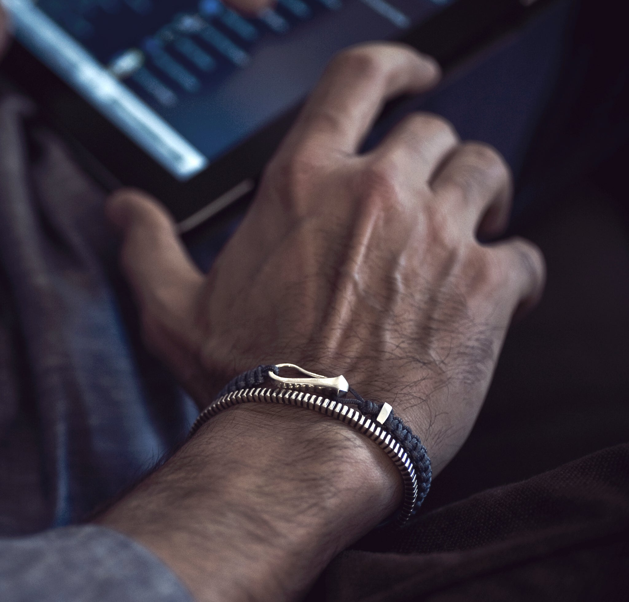 wrist of a man wearing a hook bracelet with a sterling silver ribbed cuff bracelet in sterling silver