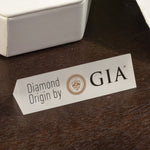 "White triangular prism plate with text ""Diamond Origin by GIA"""