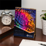 GIA desk calendar February page, featuring bright rainbow photomicrograph