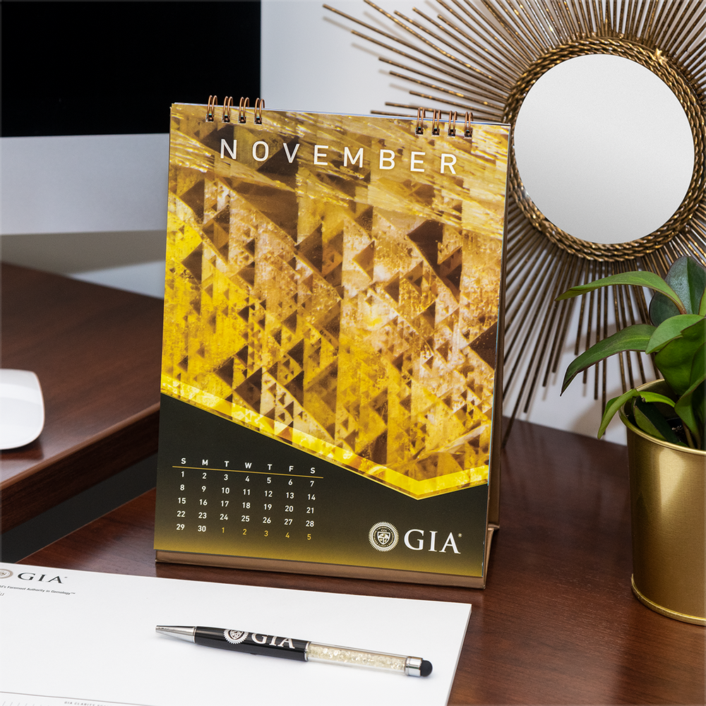 GIA desk calendar November page, featuring yellow geometric photomicrograph