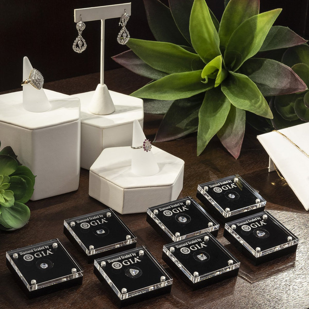 Group of 7 loose diamond display cases on counter with rings, earrings, and succulents