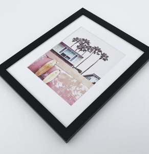 A bright pink photo print of California beach house and surfing boards