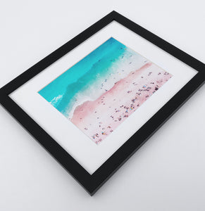 A bright azure and pink aerial photo print of a Californian coast in a black frame