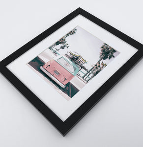 A bright pink aerial photo print of a surfing miniwan in a black frame